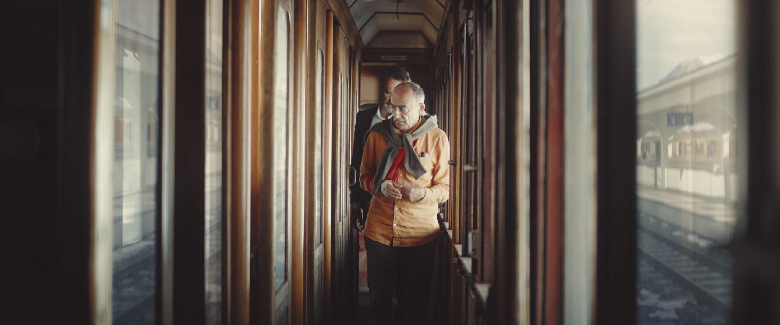 two men walking down train aisle